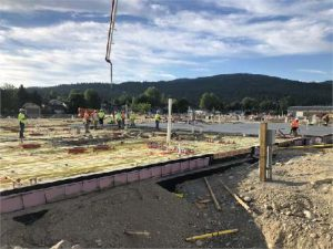 Construction photo of a concrete slab pour. Blue skies, trees and hills in the background