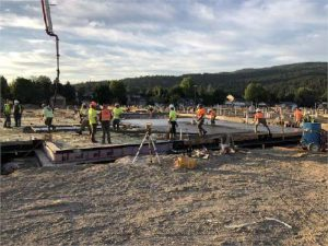 Construction photo of a concrete slab pour. Blue skies, trees and hills in the background. Slightly different angle.